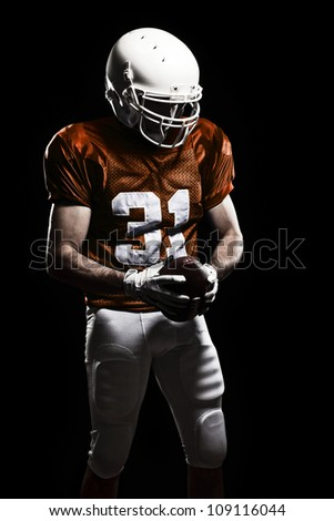 Football Player with number on the uniform, holding a ball. Studio Shot - stock photo