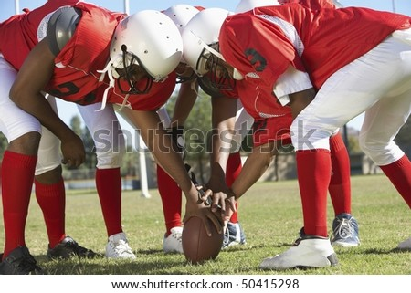 Football Players in Huddle around ball - stock photo