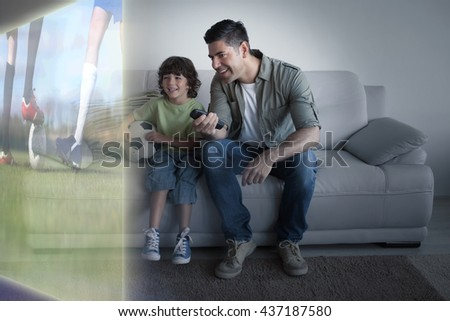 Football players tacakling for the ball on pitch against father and son with football watching tv in the living room - stock photo