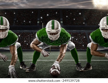 Football Players with a green uniform on the scrimmage line, on a stadium. - stock photo