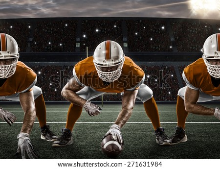 Football Players with a orange uniform on the scrimmage line, on a stadium. - stock photo