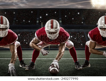 Football Players with a red uniform on the scrimmage line, on a stadium. - stock photo
