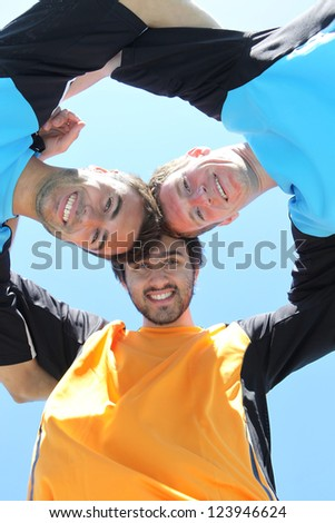 Football players with heads together - stock photo