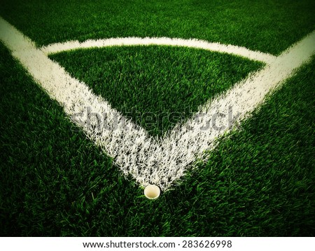 Football playground corner on artificial green turf ground with painted white line marks. Milled black rubber in basic. - stock photo