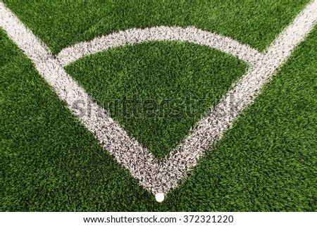 Football playground corner on heated artificial green turf ground with painted white line marks. Milled black rubber in basic of ground. - stock photo