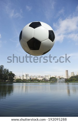 Football soccer ball flying in the sky above tranquil lake in Ibirapuera Park with Sao Paulo Brazil city skyline - stock photo