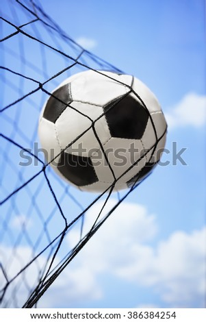 Football soccer ball in back of the net concept for goal, scoring, winning and team competition - stock photo