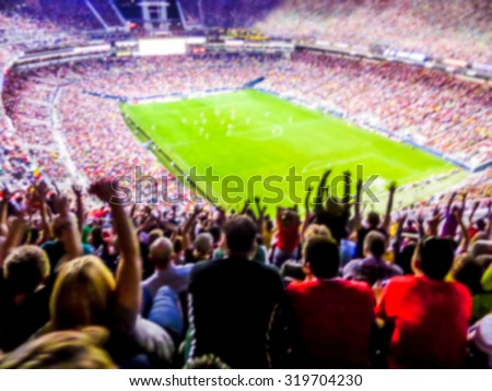 Football- soccer fans support their team and celebrate goal in full stadium with open air with nice sky.-blur picture. - stock photo