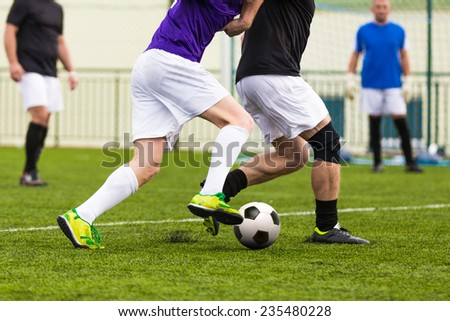 football soccer game. competition between two running players footballers - stock photo