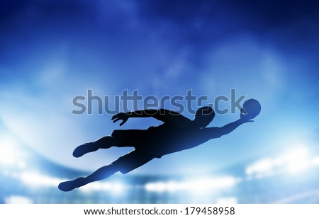 Football, soccer match. A goalkeeper jumping to defend, save the ball from goal. Lights on the stadium at night. - stock photo