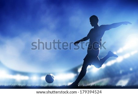 Football, soccer match. A player shooting on goal. Lights on the stadium at night. - stock photo