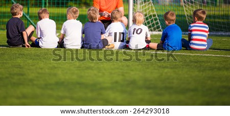 Football soccer match for children. Kids waiting on the game. briefing with trainer - stock photo