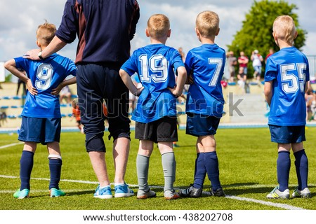 Football soccer match game for children. Youth sports team with soccer coach during football match at the stadium. Kids reserve players waiting on a bench with coach and watching soccer match. - stock photo
