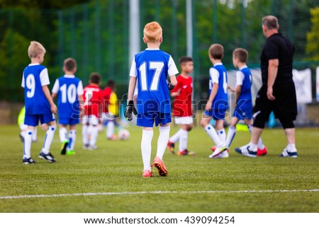 Football soccer match game for children. Youth sports team with soccer coach during football match at the stadium. - stock photo