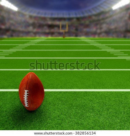 Football stadium full of fans with football in ready position on the field. Deliberate focus on ball and foreground with shallow depth of field on background. Floodlights flare for effect. Copy space.