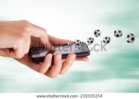 Football subject, hand holding mobile phone on blurry fast background. - stock photo