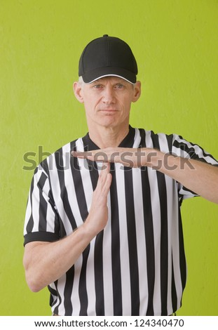 Football umpire against green background hand gesturing a time out - stock photo