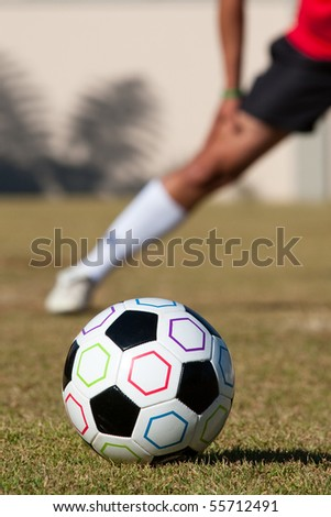 Football with man stretching in background - stock photo