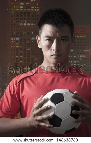 Footballer holding ball to chest with skyscraper on the background - stock photo