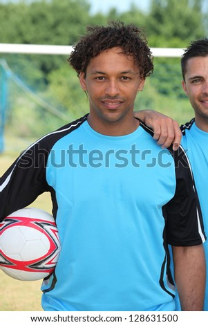 Footballer standing in front of goal - stock photo