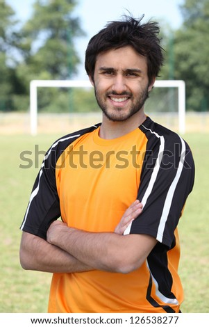 Footballer with arms crossed standing on pitch with goal in the background