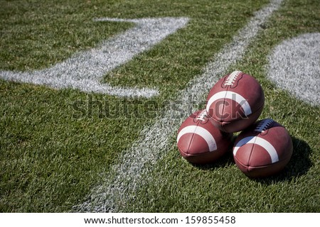 Footballs on a playing field - stock photo