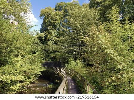 Footbridge crossing water in the woods of Skipton Castle. - stock photo