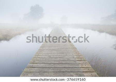 Footbridge ends in a foggy landscape  - stock photo