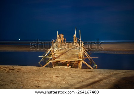 Footbridge on beach at night - stock photo