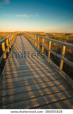 Footbridge to the sea at sunset near the San Pedro del Pinatar. Region of Murcia. Spain - stock photo