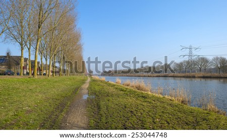 Footpath along a canal in winter - stock photo