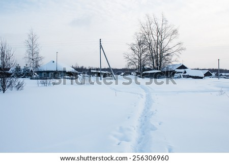 footpath in snow in traditional russian village - stock photo
