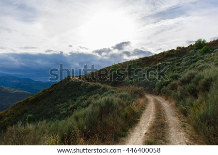 Footpath in the mountains with cloudy sky - stock photo