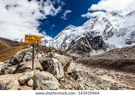 Footpath to Mount Everest Base Camp signpost in Himalayas, Nepal. Khumbu glacier and valley snow on mountain peaks, beautiful view landscape - stock photo