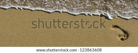 Footprint at beach with waves - stock photo