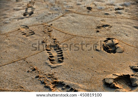 Footprint in sand. Beautiful sunset at tropical ocean beach in vintage style - stock photo