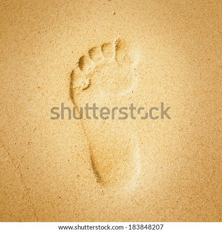 Footprint in the yellow sand on the beach