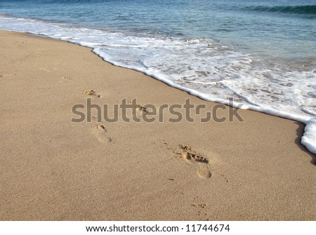 Footprint on sand and sea foam in beach - stock photo