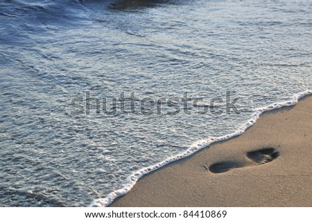 Footprint on the sandy beach and sea wave