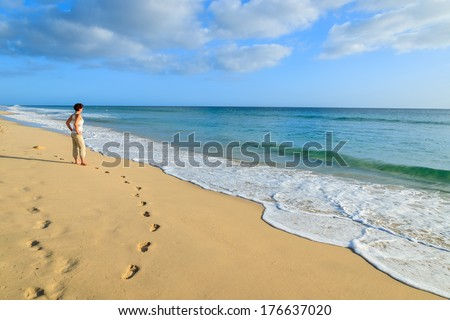 Footprints in sand and young woman standing on beach in Morro Jable town on Jandia peninsula, Fuerteventura, Canary Islands, Spain