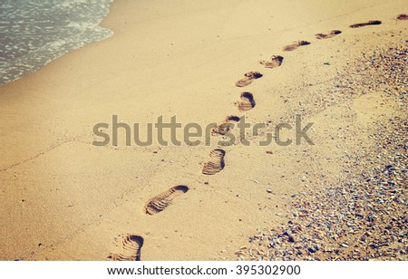 Footprints in the sand and dry autumn leaves, nature background - stock photo