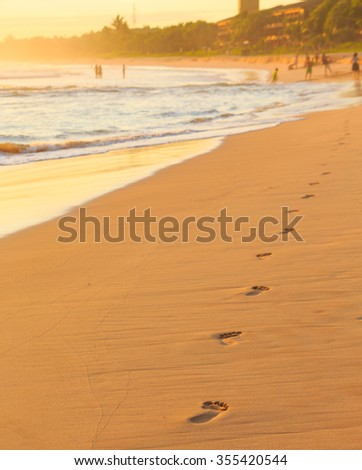 Footprints in the sand at the beach at sunset - stock photo