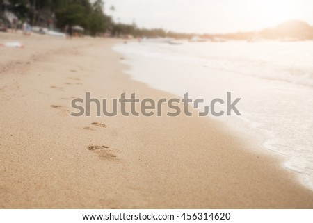 Footprints in the sand beach, selective focus with morning sun light - stock photo