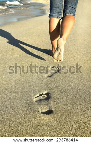 footprints in the sand near the sea - stock photo