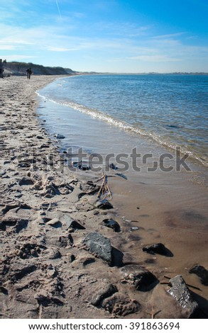 Footprints in the Sand on a Beach Shoreline - stock photo
