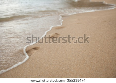 footprints in the sand on a beach washes off a wave. blurs. background. - stock photo