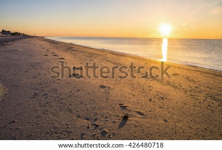 Footprints in the sand, sunset at the seaside - stock photo