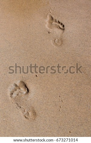 Footprints left in the sand by bare feet