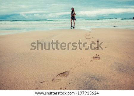 Footprints left on the beach by a young woman - stock photo