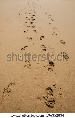 Footprints of hiking boots on the sand of a beach.